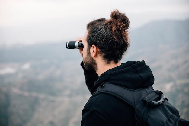 Mężczyzna wycieczkowicz z plecakiem patrząc przez lornetkę widok na góry