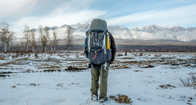 Mężczyzna wycieczkowicz z plecakiem stoi plecami, patrząc na ośnieżone góry przed sobą. droga do osiągnięcia celu