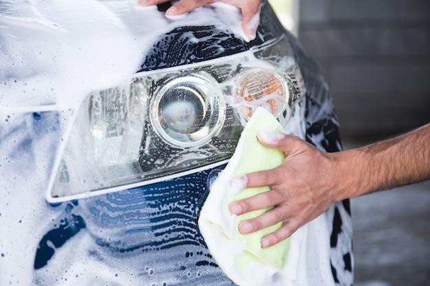Mężczyzna wyciera piankę na samochodzie szmatką. myjnia samochodowa