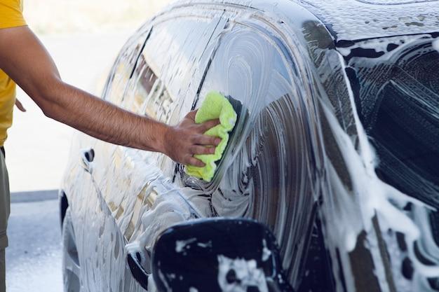 Mężczyzna Wyciera Piankę Na Samochodzie Szmatką. Myjnia Samochodowa Premium Zdjęcia