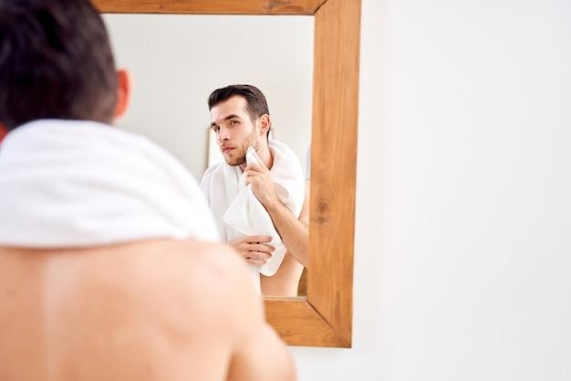 Mężczyzna wyciera ręcznik, stojąc przy lustrze w wannie rano