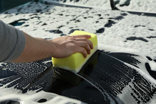 Mężczyzna wyciera samochód gąbką.