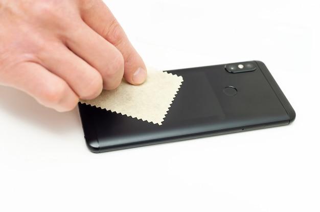 Mężczyzna wyciera smartfon ściereczką z mikrofibry