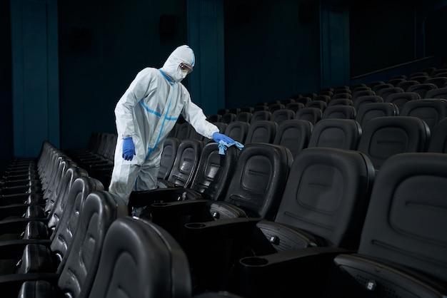 Mężczyzna wyciera szmatą krzesła w sali kinowej