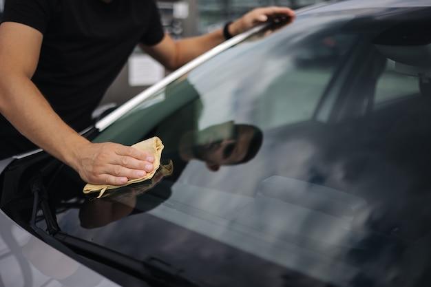 Mężczyzna wyciera szmatą przednią szybę swojego samochodu w salonie na myjni samoobsługowej