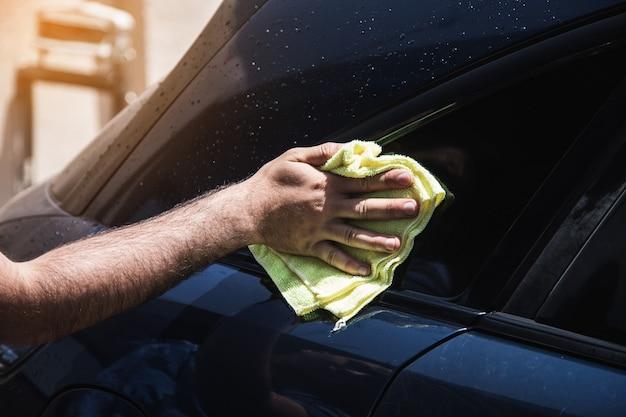 Mężczyzna wyciera szmatką mokry samochód