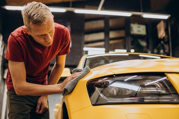 Mężczyzna wycierający samochód mikrofibrą po umyciu