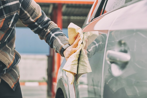 Mężczyzna wycierający samochód po umyciu w myjni