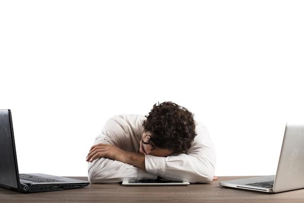Mężczyzna wyczerpany przepracowaniem, spaniem przy komputerze