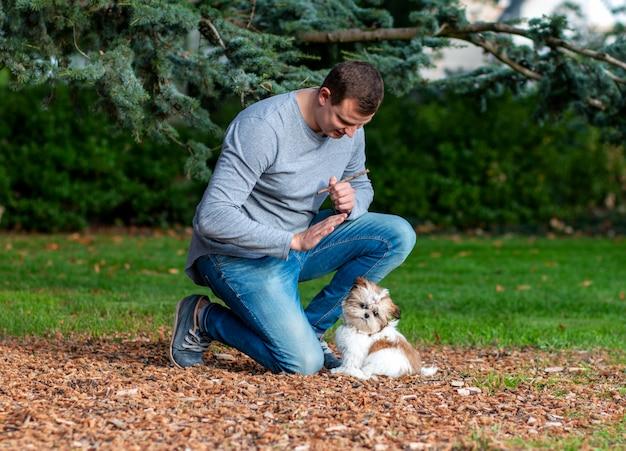 Mężczyzna wydaje polecenia psu, szkoląc szczeniaka na zewnątrz