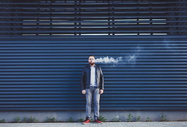 Mężczyzna wydycha chmurę dymu