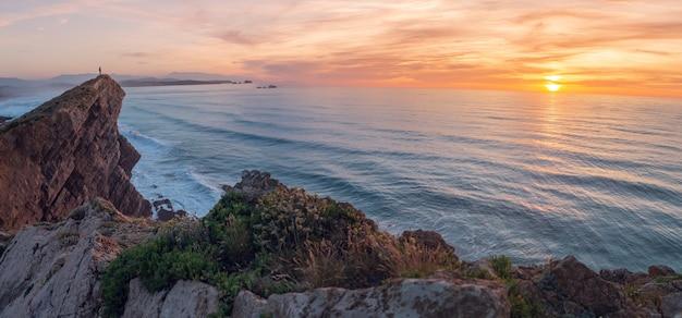 Mężczyzna wygląda na morze z klifu o zachodzie słońca.
