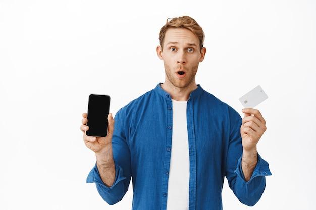 Mężczyzna wygląda na zaskoczonego, pokazuje ekran telefonu komórkowego i kartę kredytową, mówiąc o funkcji banku, ofercie zakupów online, stojąc zdumiony na białej ścianie
