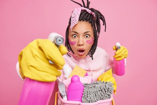Mężczyzna wygląda z wyrazem omg trzyma środki czystości gotowe do posprzątania pokój przechodzi zabiegi kosmetyczne, pozując w pomieszczeniu na różowo