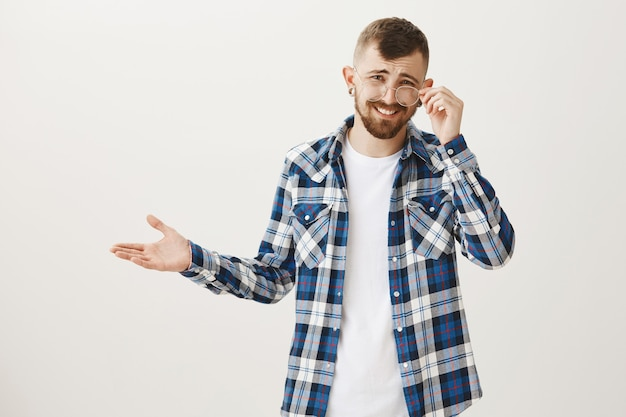 Mężczyzna wyglądający na niewzruszonego, szydzący z głupoty, założył okulary