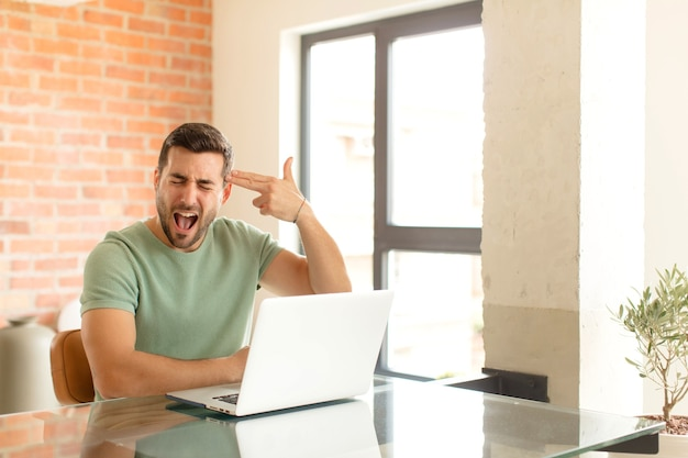 Mężczyzna wyglądający na niezadowolonego i zestresowanego, samobójczy gest wykonujący znak pistoletu ręką, wskazujący na głowę