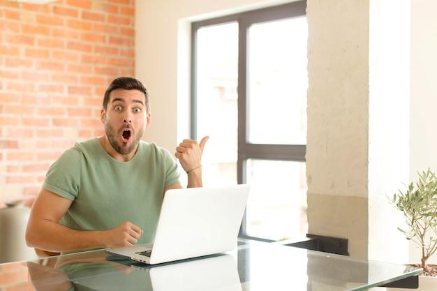 Mężczyzna wyglądający na zdziwionego z niedowierzaniem, wskazujący na przedmiot z boku i mówiący wow, niewiarygodne