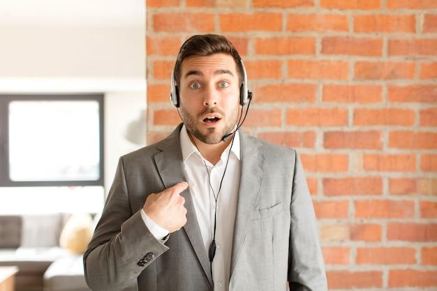 Mężczyzna wyglądający na zszokowanego i zaskoczonego z szeroko otwartymi ustami, wskazujący na siebie