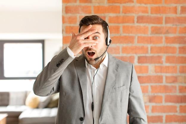 Mężczyzna wyglądający na zszokowanego, przestraszonego lub przerażonego, zakrywający twarz dłonią i zaglądający między palce
