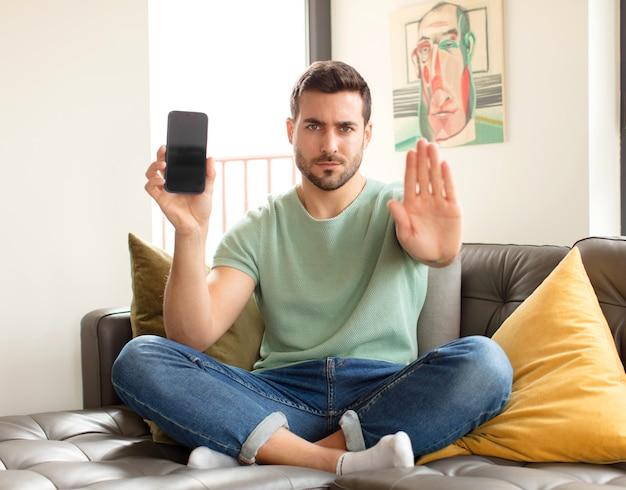 Mężczyzna wyglądający poważnie, surowo, niezadowolony i zły pokazując otwartą dłoń, wykonując gest zatrzymania