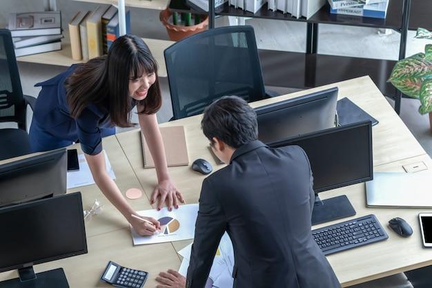 Mężczyzna wyjaśnia pracę dziewczynie przy biurku.