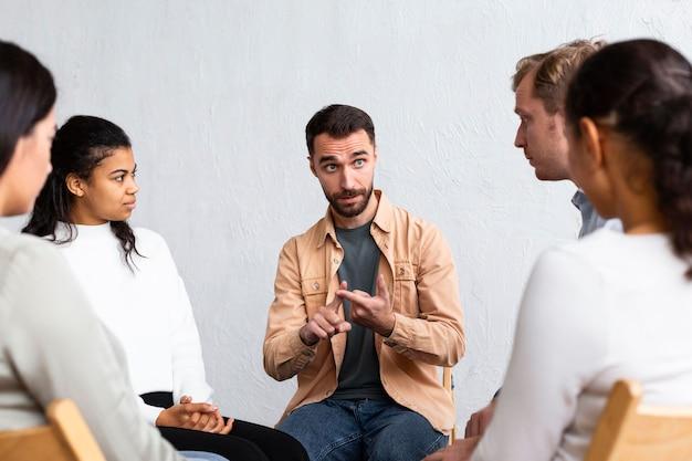 Mężczyzna wyjaśniający swoje problemy na sesji terapii grupowej