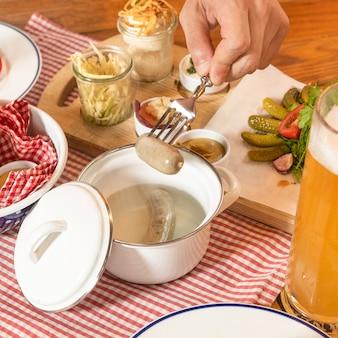 Mężczyzna wyjmujący gorącą niemiecką kiełbasę z piwem