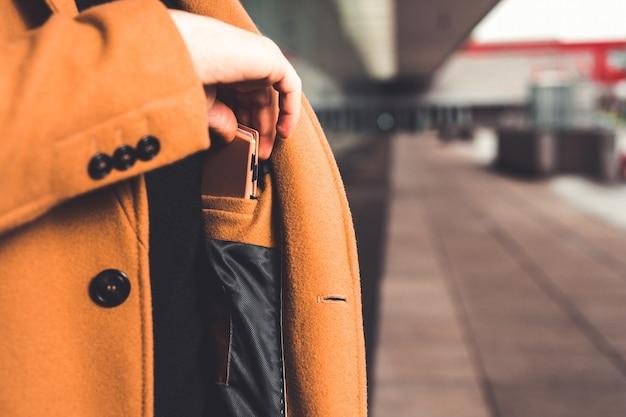 Mężczyzna wyjmujący portfel z wewnętrznej kieszeni płaszcza