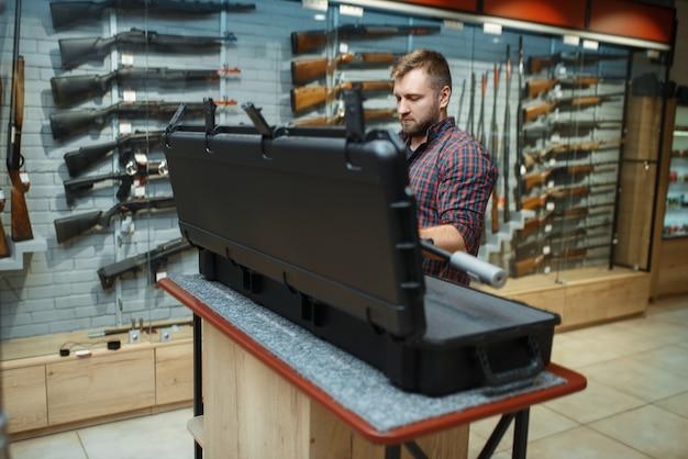 Mężczyzna wyjmuje karabin snajperski z walizki w sklepie z bronią