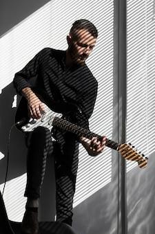 Mężczyzna wykonawca gra na gitarze elektrycznej z cieniami rolet okiennych