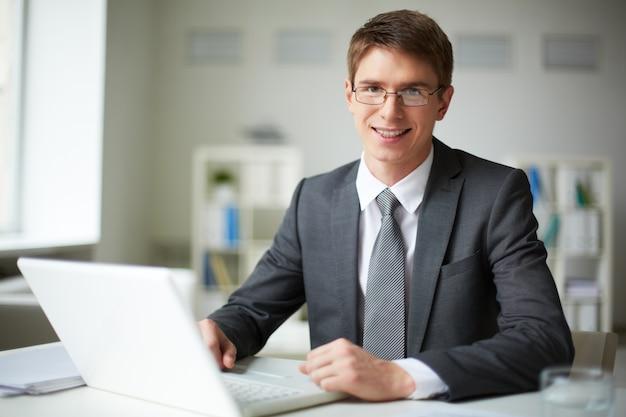 Mężczyzna wykonawczej z okularami pisze na laptopie