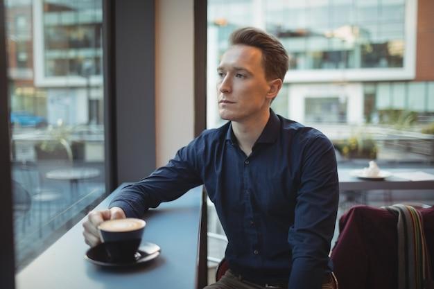 Mężczyzna wykonawczy kawie przy ladzie