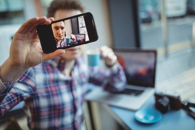 Mężczyzna wykonawczy przy selfie z telefonu komórkowego