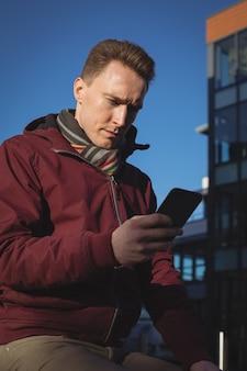 Mężczyzna wykonawczy za pomocą telefonu komórkowego