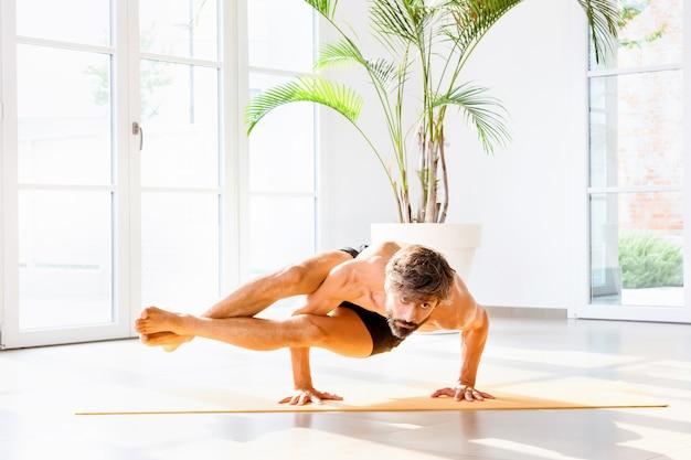 Mężczyzna wykonujący astavakrasana lub ośmiokątną pozę, balansując na ramionach