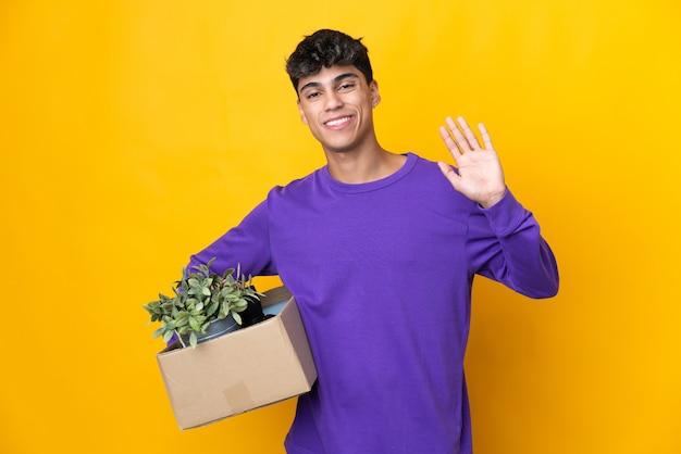 Mężczyzna wykonujący ruch, podnosząc pudełko pełne rzeczy, salutując ręką z radosnym wyrazem twarzy