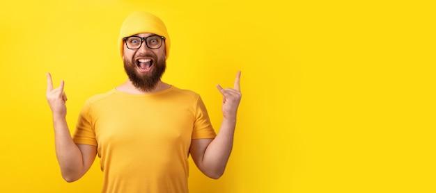 Mężczyzna wykonuje gest rock n roll na żółtym tle, panoramiczny układ