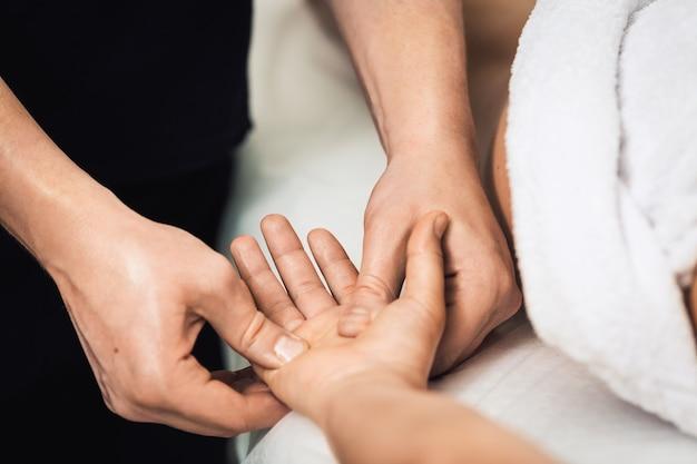 Mężczyzna wykonuje masaż dłoni i palców w spa. pojęcie zdrowego stylu życia.