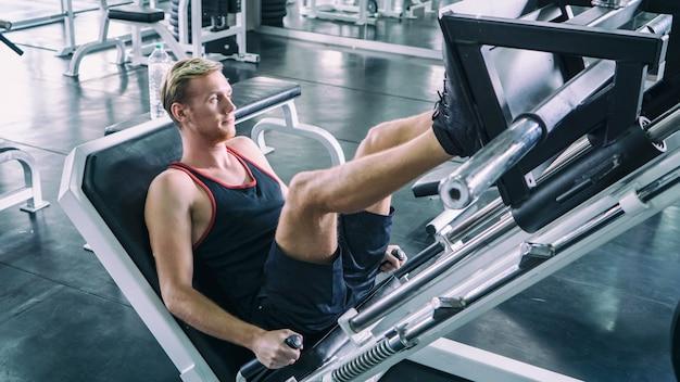 Mężczyzna wykonuje nogę na maszynie w fitness