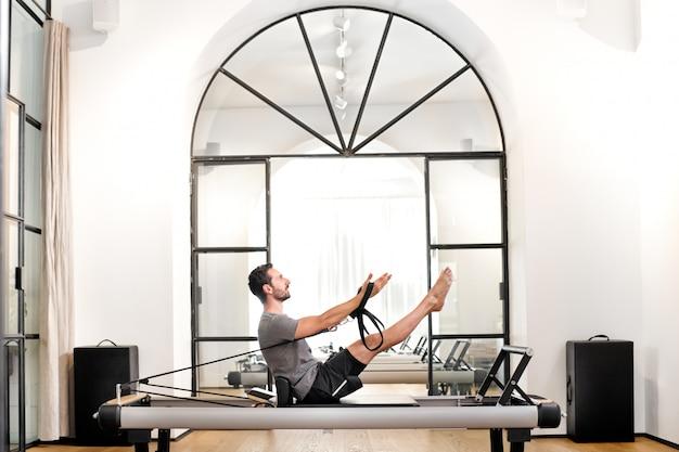 Mężczyzna wykonuje pilates zwiastuna ćwiczenie w gym