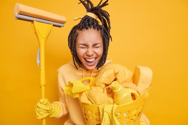 Mężczyzna wykonuje prace domowe trzyma mopa do mycia podłogi w domu niesie kosz z koszem na pranie z detergentami czyszczącymi na żółto