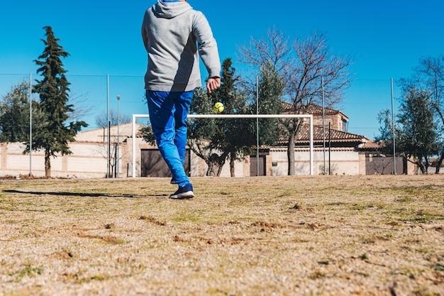 Mężczyzna wykonuje rzut wolny w kierunku bramki. boisko do piłki nożnej.