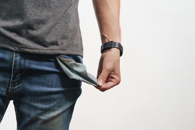 Mężczyzna wykręcający kieszeń dżinsów, aby pokazać pustą kieszeń. bankrut, zła gospodarka, brak koncepcji pieniędzy.