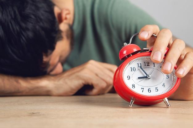 Mężczyzna wyłącza alarm przy stole