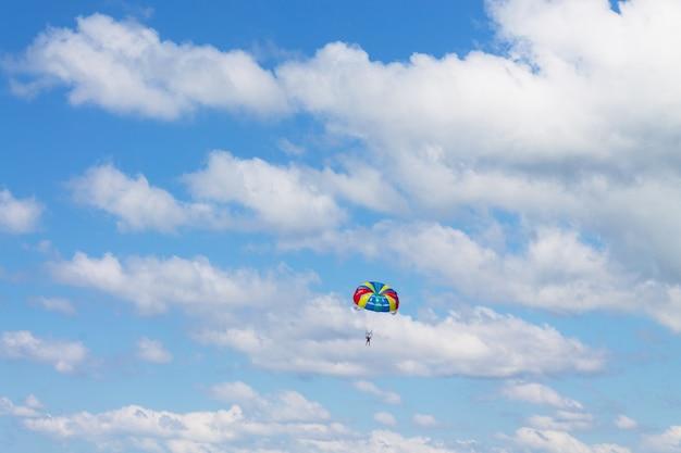 Mężczyzna wylatuje w błękitne niebo na sportowym spadochronie. styl życia