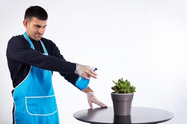 Mężczyzna wylewa w domu wodę na kwiatek z rozpylacza