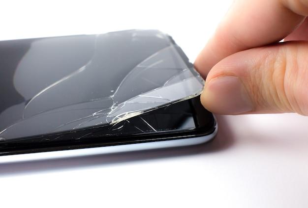 Mężczyzna wymienia zepsutą osłonę ekranu ze szkła hartowanego na smartfona. ścieśniać.