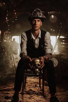 Mężczyzna wynalazca w steampunkowym garniturze w cylindrze z okularami ze złotą czaszką w dłoni