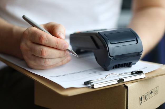 Mężczyzna wypełnia dokument dostawy do domu na pudełku