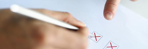 Mężczyzna wypełnia kolumny testowe czerwonym długopisem